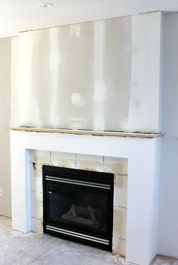 Fireplace Makeover PROGRESS - Adding new drywall to cover up the texture before installing the mantel, trim and marble subway tile - Satori Design for Living