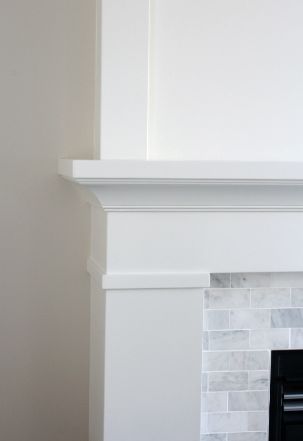 White Painted Fireplace Mantel with Marble Subway Tile Surround