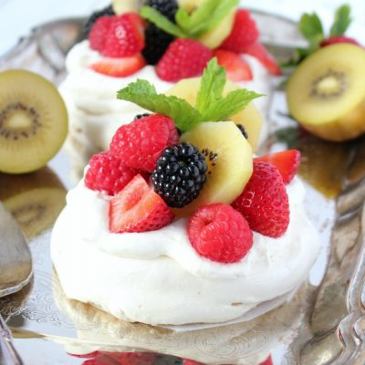 Try this easy summer pavlova recipe with light and airy meringue surrounded by a crisp crust topped with a mountain of whipped cream and fresh seasonal fruit - Satori Design for Living