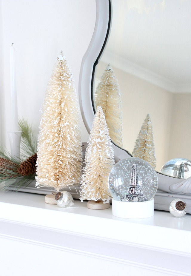 Snow Covered Bottle Brush Trees on White Fireplace Mantel