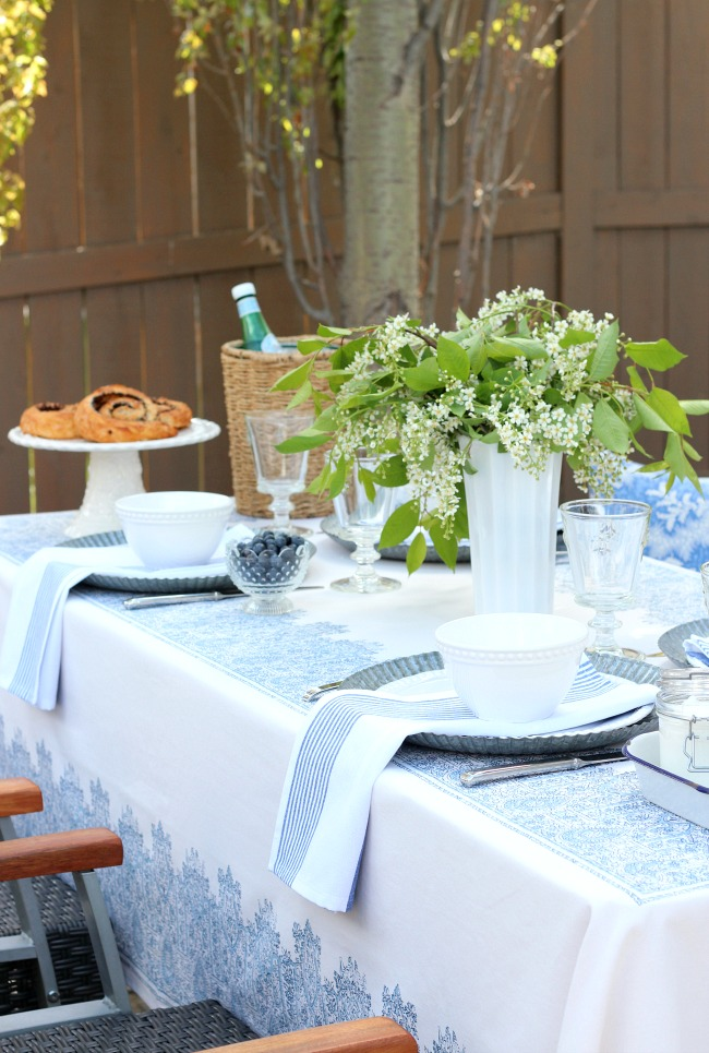 Casual Outdoor Brunch Table Setting with Pretty White Dishes and Blue Striped Napkins - Satori Design for Living