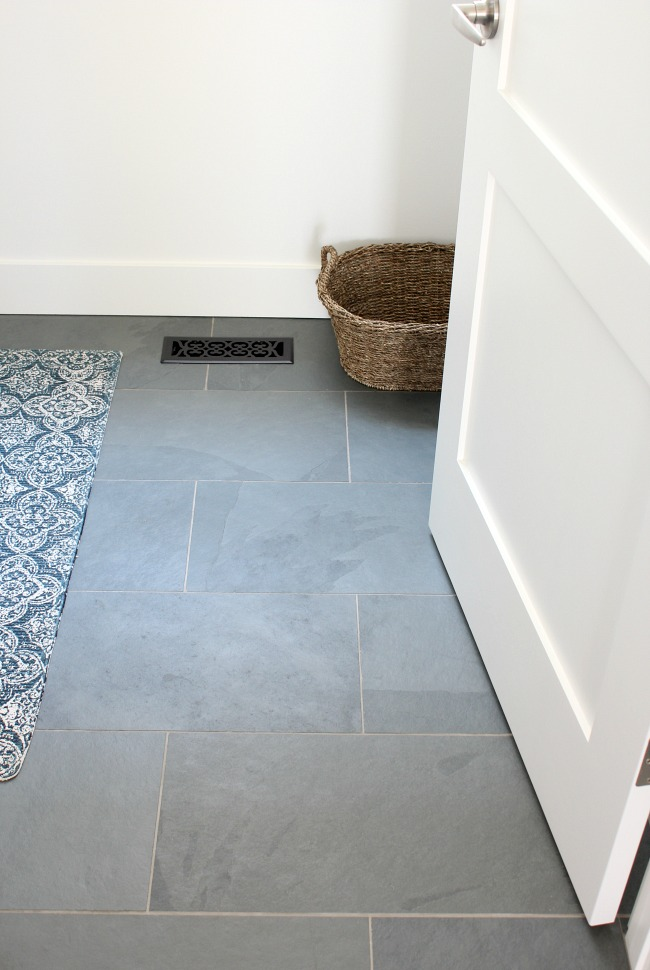 White Shaker Style Baseboards and 3-Panel Door in the Laundry Room with Brazilian Slate Floor