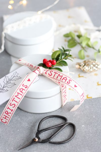 Christmas Cookies Packaged Up in White Tins with Pretty Ribbon and Greenery