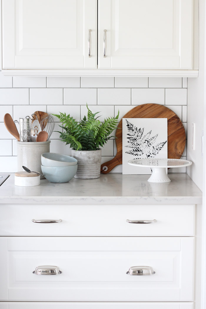 Printed Fern Art in White Kitchen with Subway Tile Backsplash