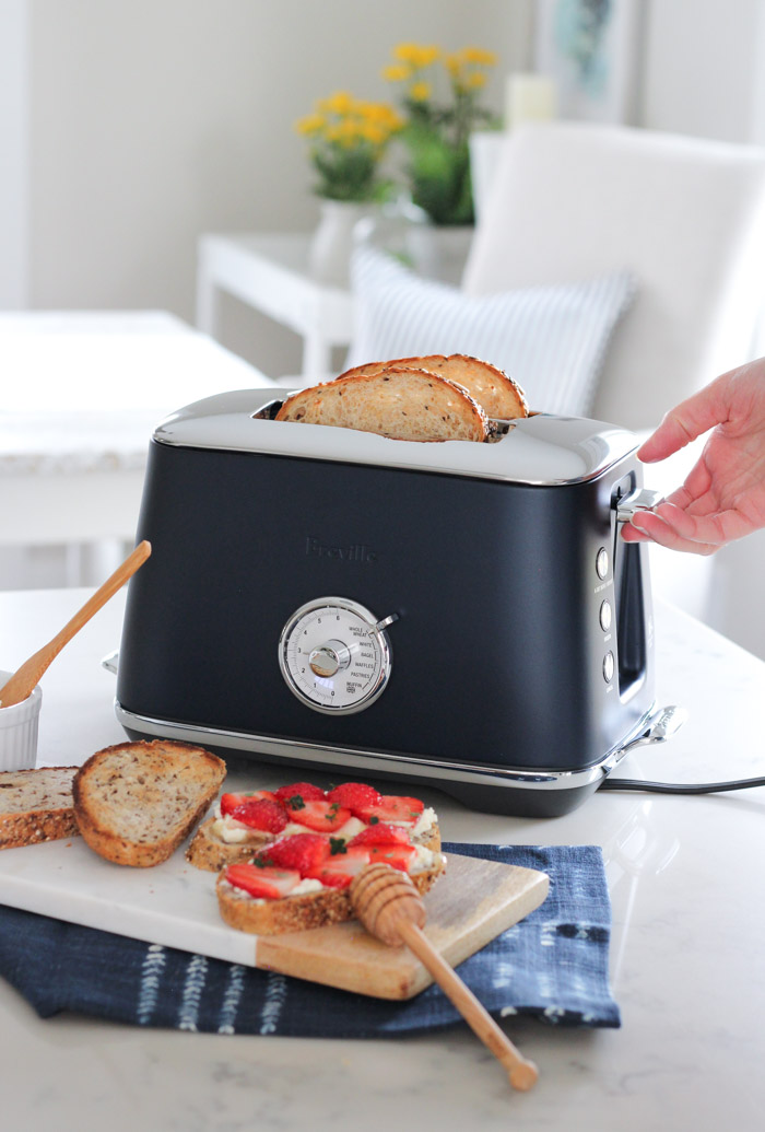 Making Toast with Blue Toaster in White Kitchen