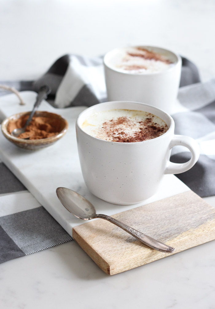 Homemade Latte with Maple Whipped Cream and Cinnamon in White Mug on Marble Board