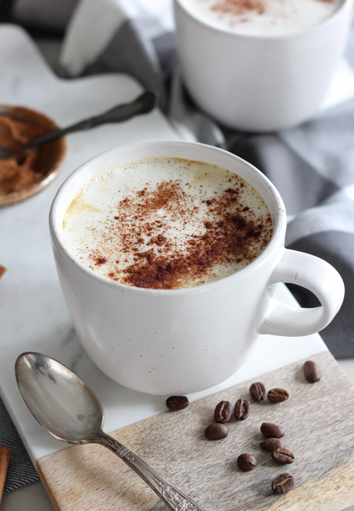Pumpkin Spice Latte with Whipped Cream and Cinnamon in White Mug