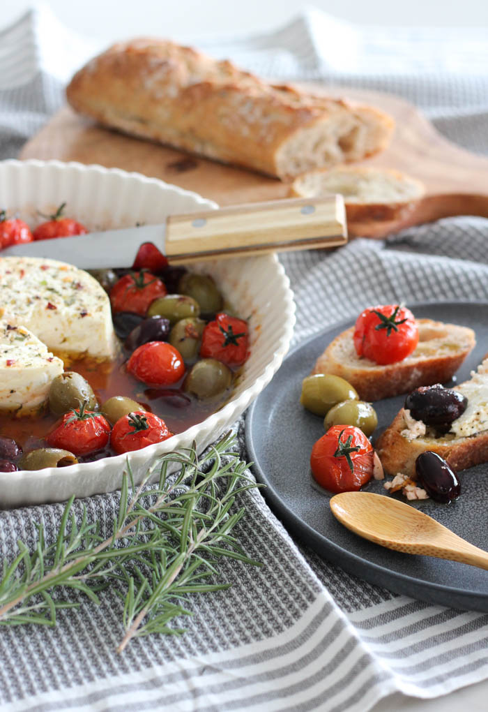Baked Feta with Tomatoes and Olives in White Dish with Crostini