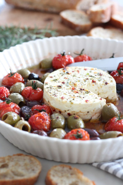 Baked Feta with Olives and Tomatoes in Dish with Crostini