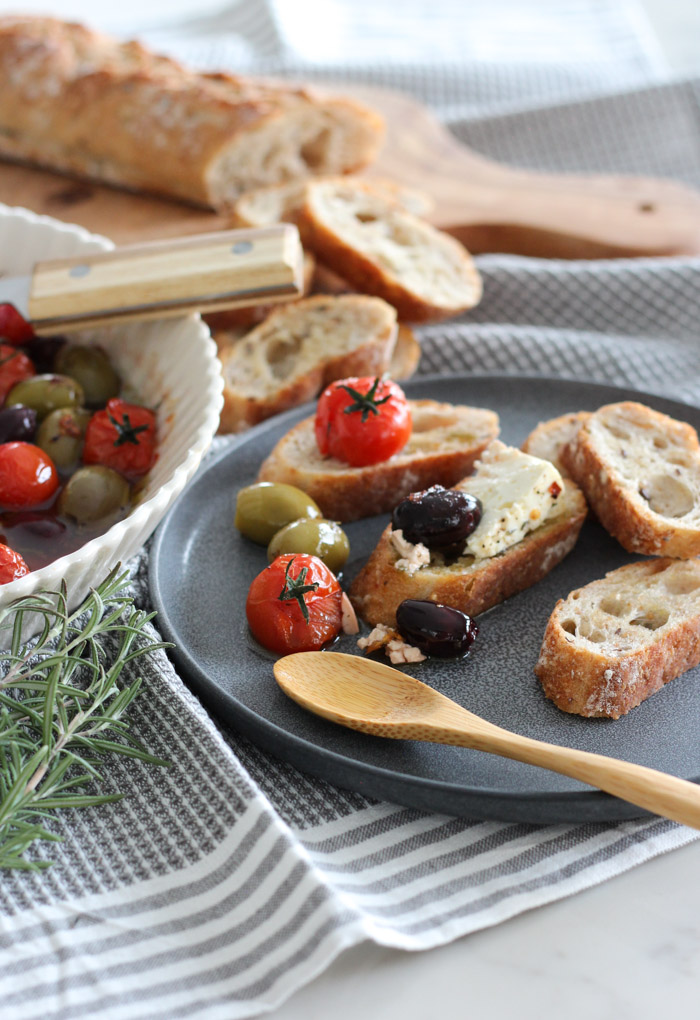 Crostini with Baked Feta, Tomatoes and Olives on a Grey Plate