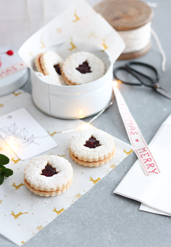 Christmas Linzer Cookies with Raspberry Jam and Powdered Sugar in White Tin