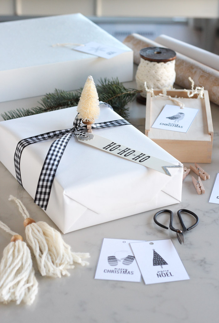Christmas Gift Wrapped in White Paper with Black Checkered Ribbon and Bottle Brush Tree Embellishment