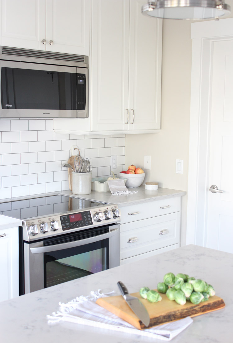 IKEA White Kitchen Cabinets with White Subway Tile Backsplash and Quartz Countertop