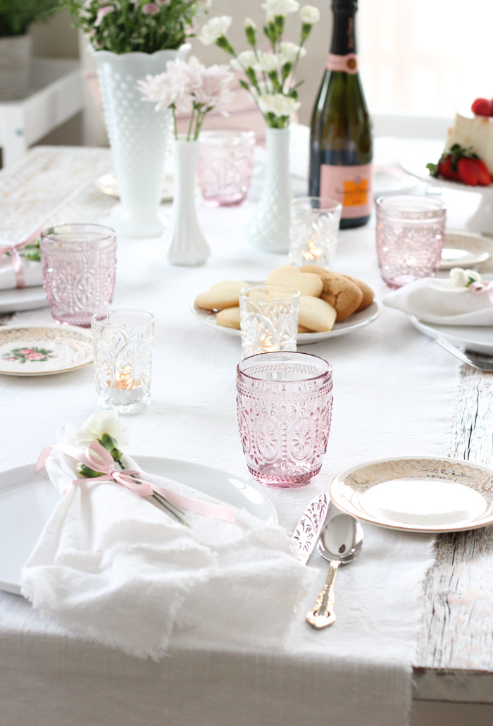 Valentine's Day Table Setting with Pink Embossed Glasses, Milk Glass Vases and Pink Champagne
