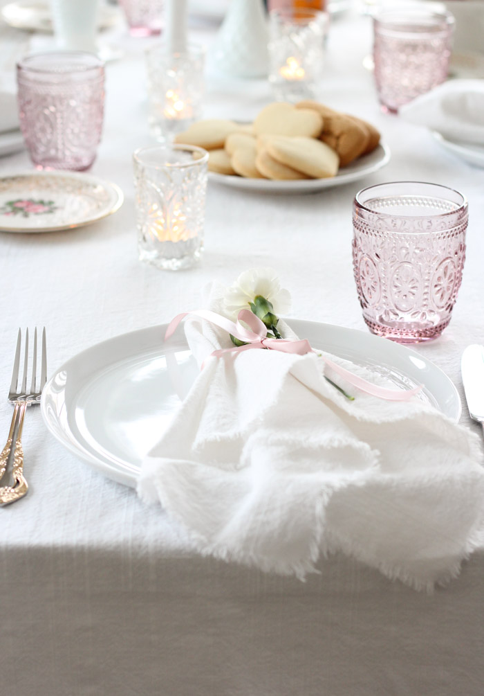 Valentine's Day Table Setting with Pink Tumblers, White Frayed Edge Napkins and Gold Flatware