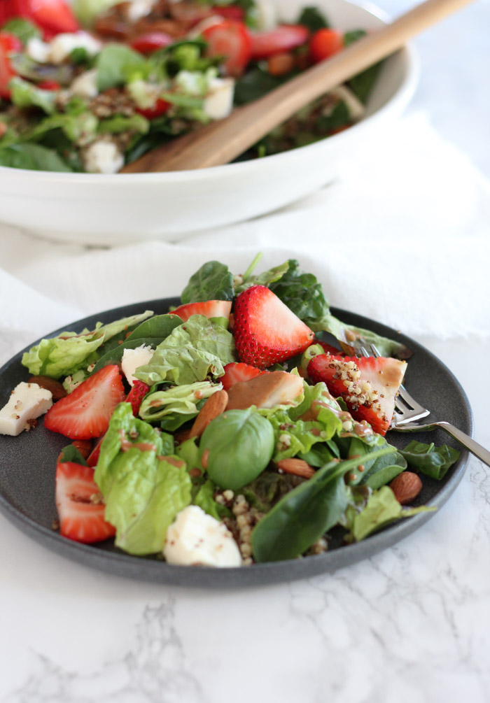 Strawberry Spinach Salad with Quinoa, Basil, Fresh Mozzarella, Cucumber and Toasted Almonds on Black Salad Plate