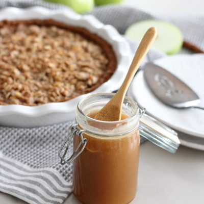 Jar of Salted Caramel Sauce with Bamboo Spoon and Apple Pie