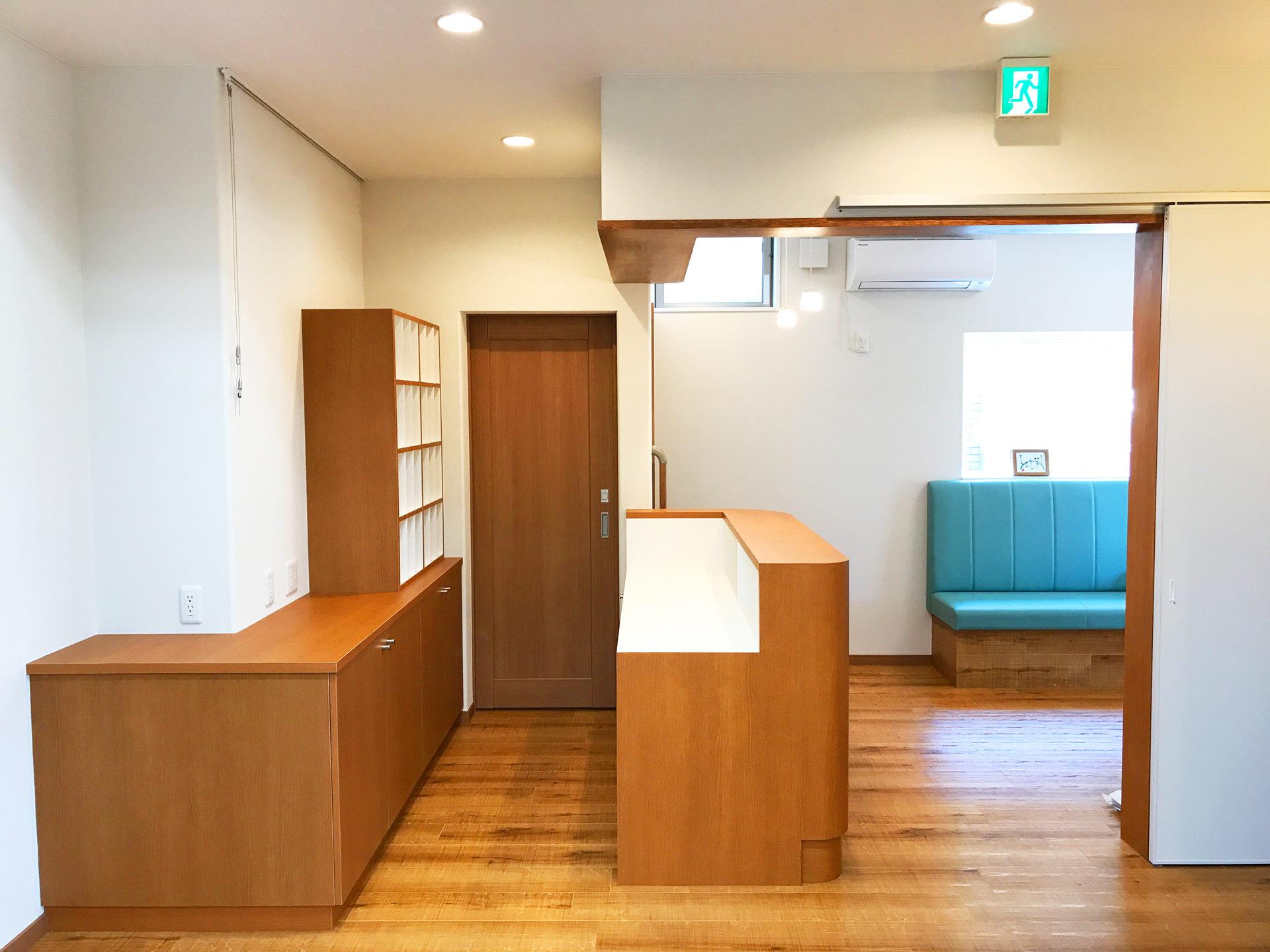 設計・デザインをした店舗(鍼灸接骨院)付き住宅の受付カウンターとカルテ棚と待合室