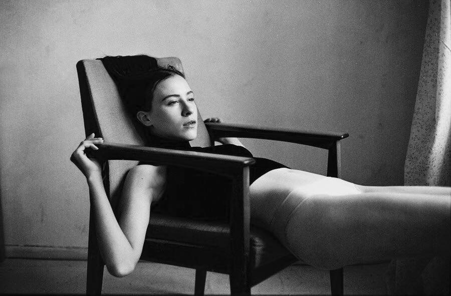 girl lying back in chair black and white