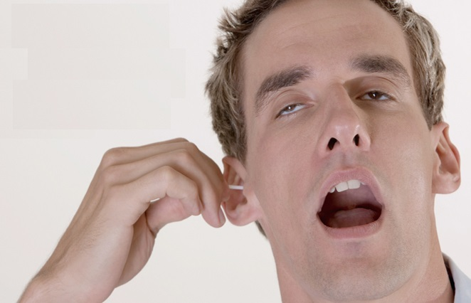 Close-up of a mid adult man cleaning his ear with a cotton swab