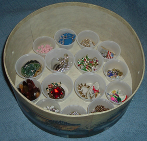 On the bottom layer of the box, I set little condiment cups to hold items used only occasionally--my Christmas pins, for instance. The 3 shelves will stack on top of this layer.