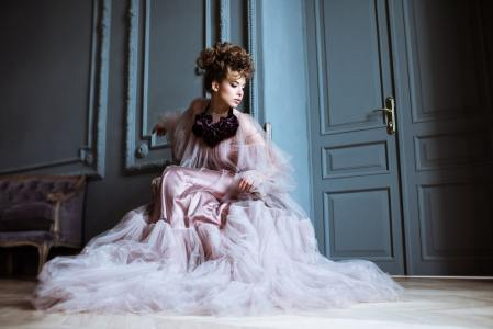 Fashionable female portrait of cute lady in pink dress indoors