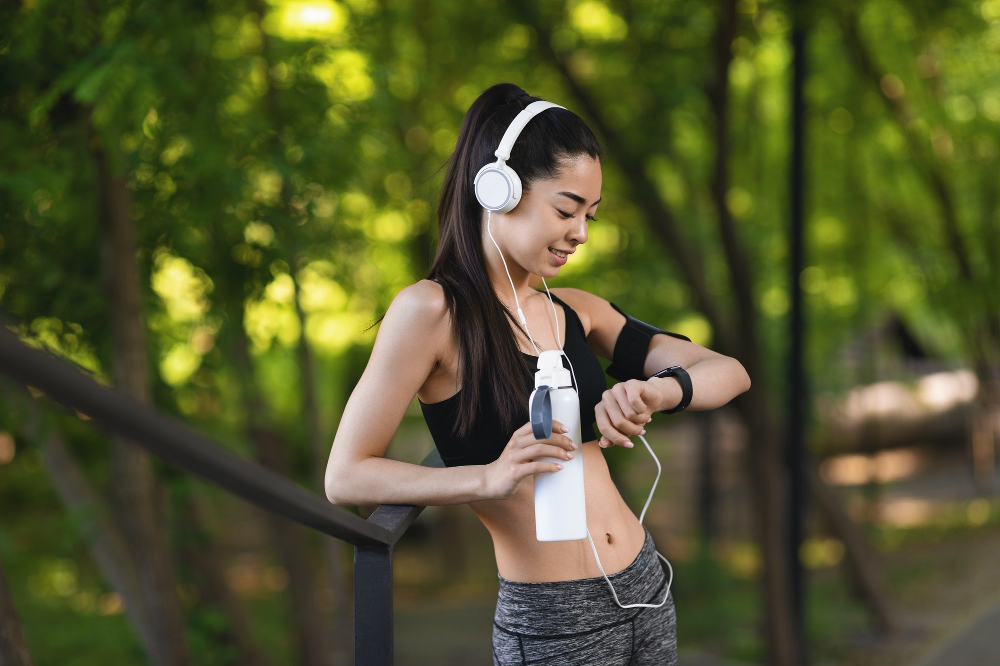 Sport Gadgets. Young Asian Jogger Woman In Headphones Looking At Smartwatch