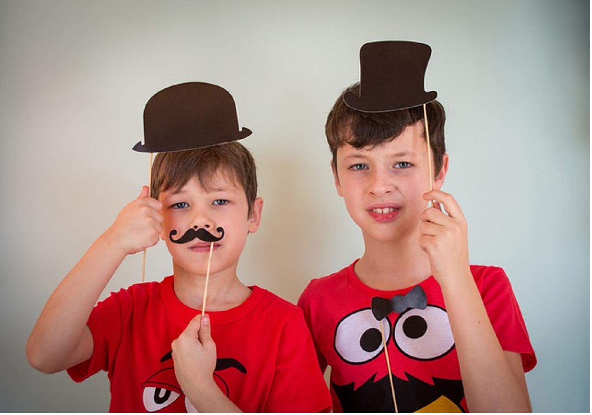 Kids using props while posing in front of the photo booth's camera
