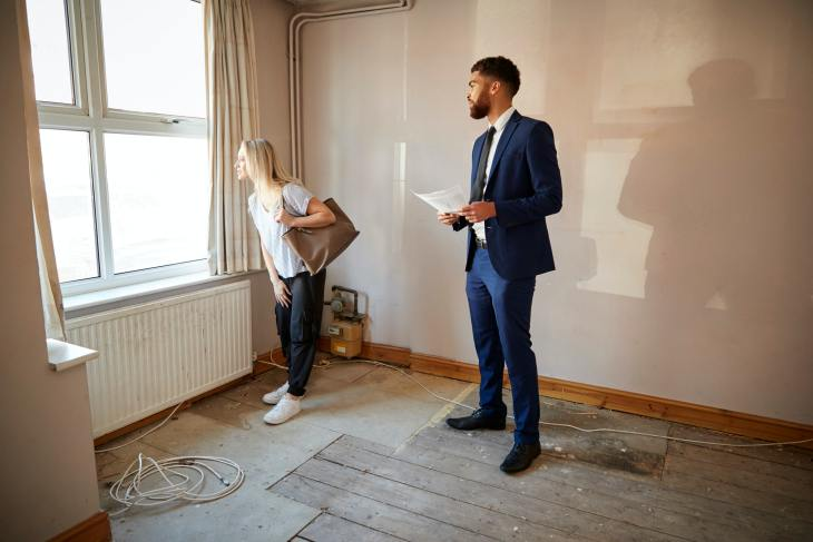 Female First Time Buyer Looking At House Survey With Realtor