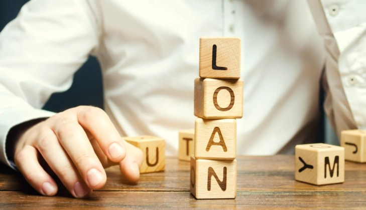 Wooden blocks with the word loan and businessman