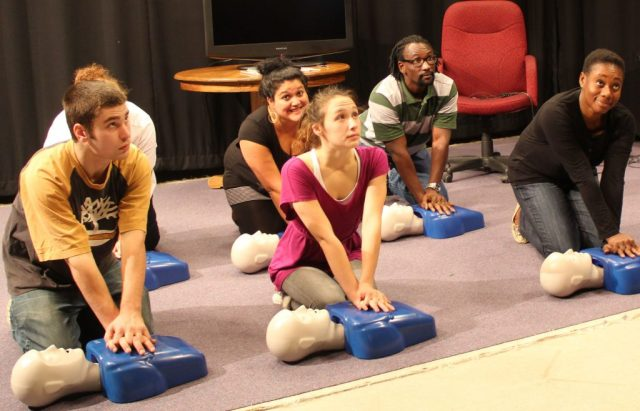 6 participants in CPR class training on mannequins