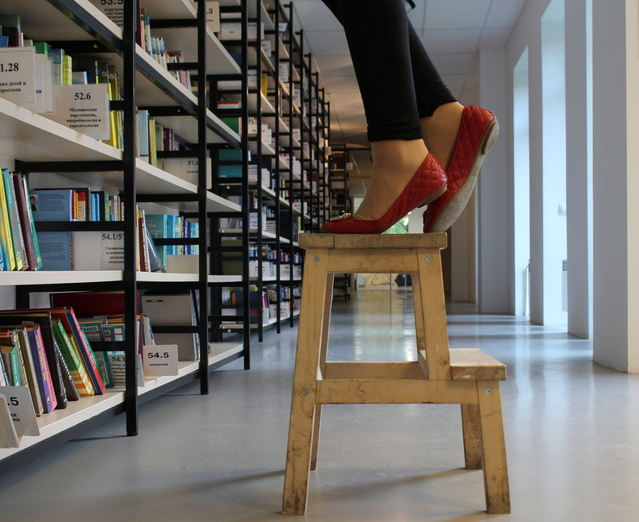 woman is balancing on the short stool while trying to reach for the book on the upper shelf