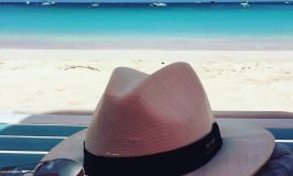 a summer hat with sunglasses laying on the beach bench with blue waters of Caribbean sea