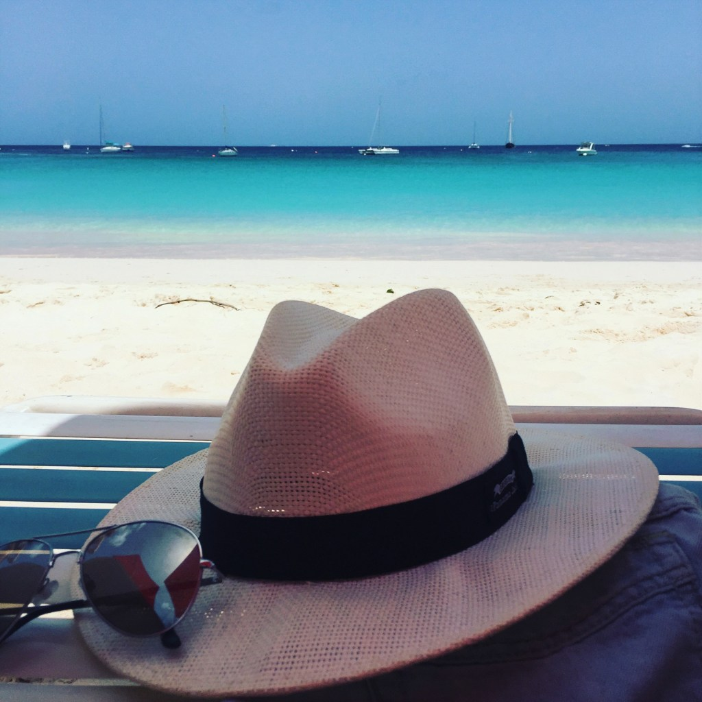 a summer hat with sunglasses laying on the Caribbean beach bench