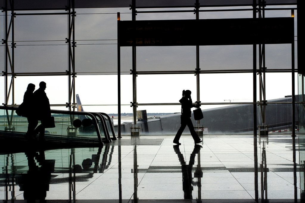 a woman walking along tall glass windows of airport