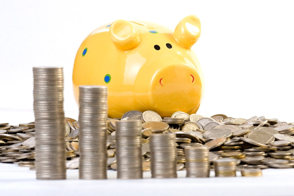 piggy bank and a pile of coins in front of it-retirement income