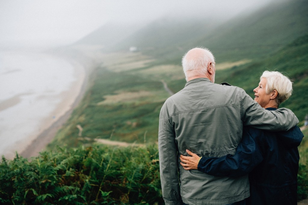 Baby boomer's couple looking at misty water and green field