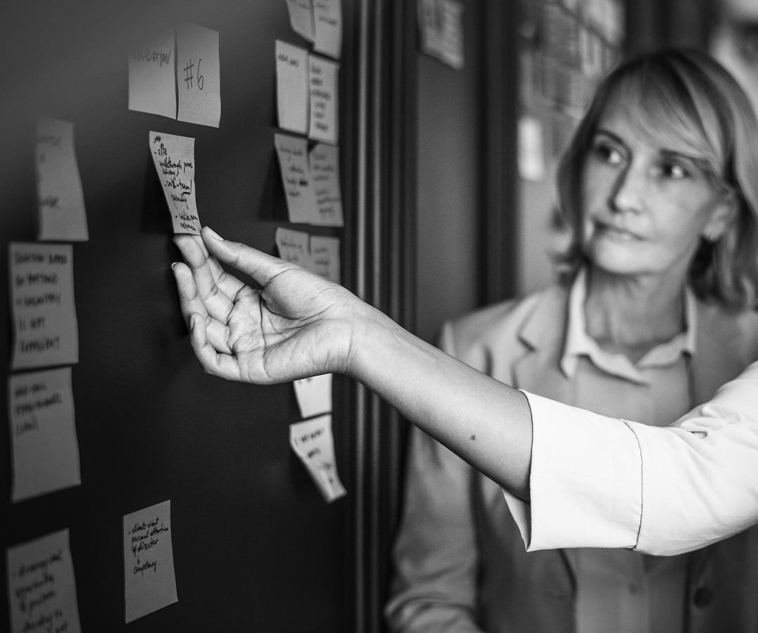 women planning tasks w/ sticky notes-organize finances for retirement