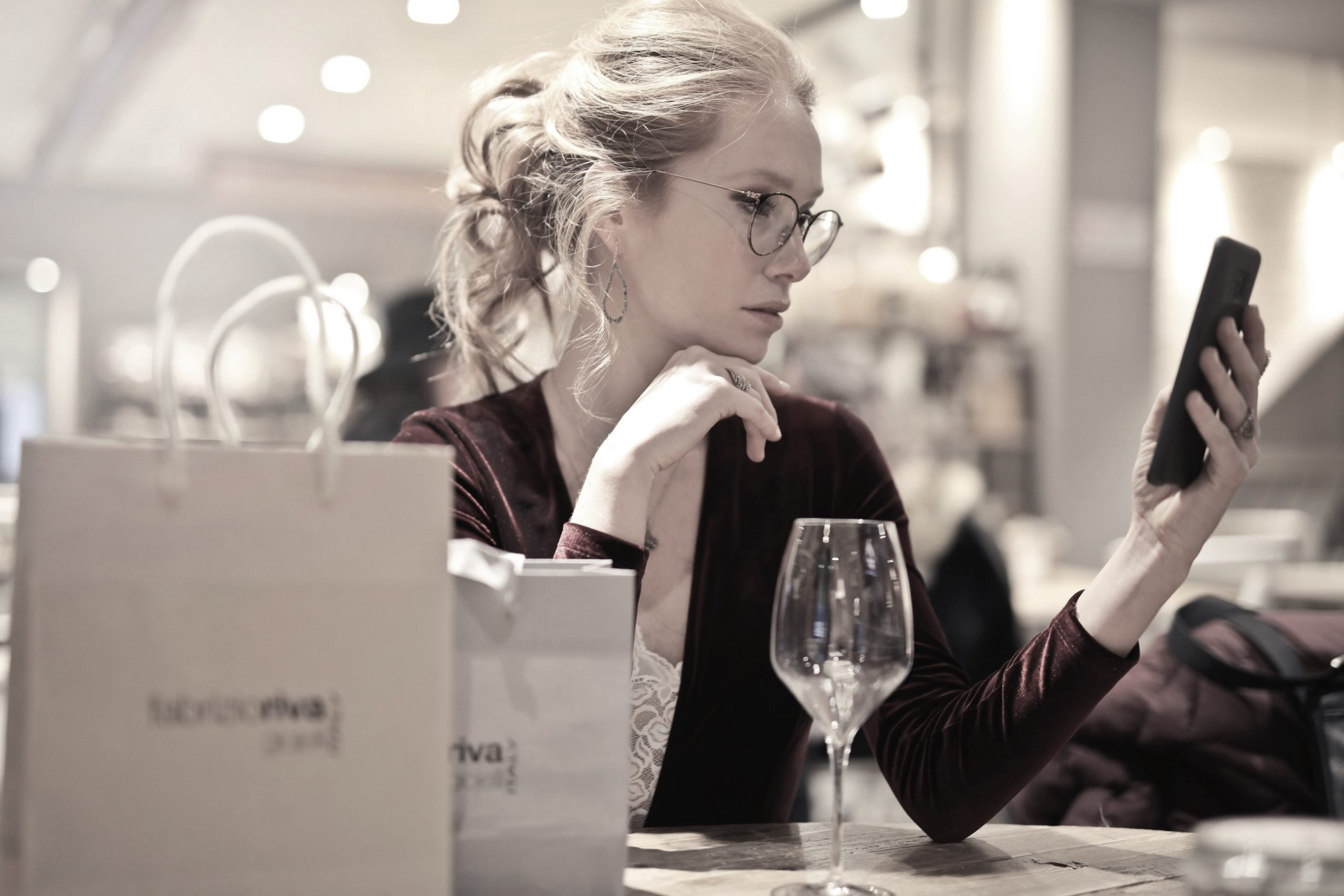 young woman at the table with a phone - alternatives to traditional retirement