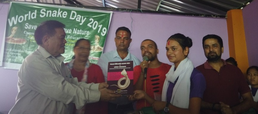 Dr. Chhabilal Thapa distributing book to Hema Poudel who secured first position