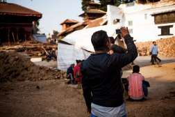 nepali people taking pictures of the disaster