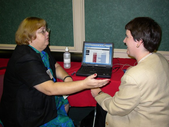Two women seated in front of a laptop