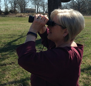 Pam watching birds on her property with binoculars.