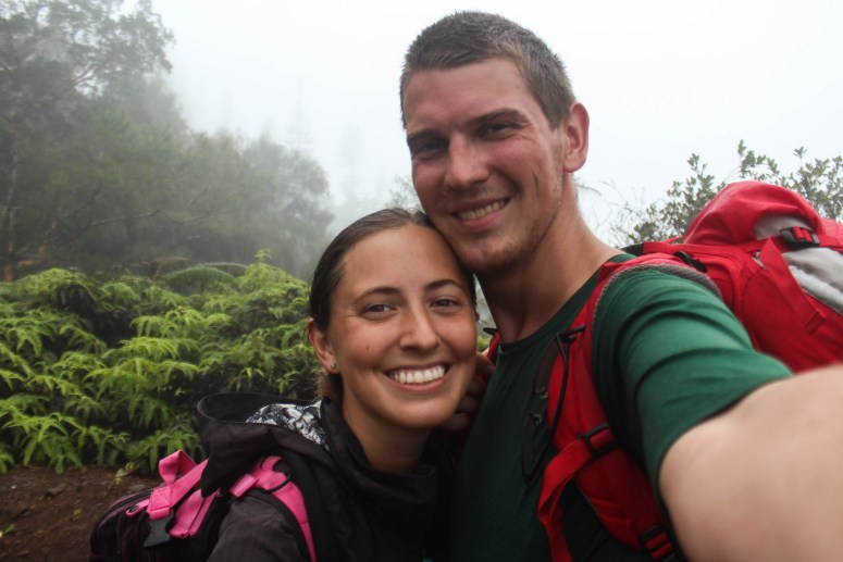 two people smiling on cloudy mountain top