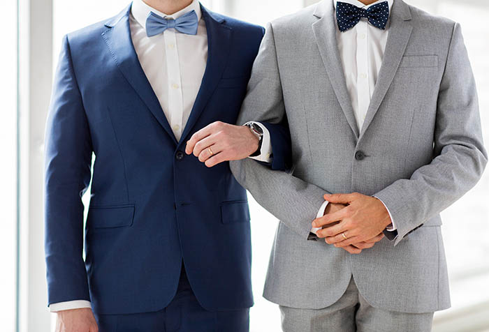 Two men in suits with arms hooked