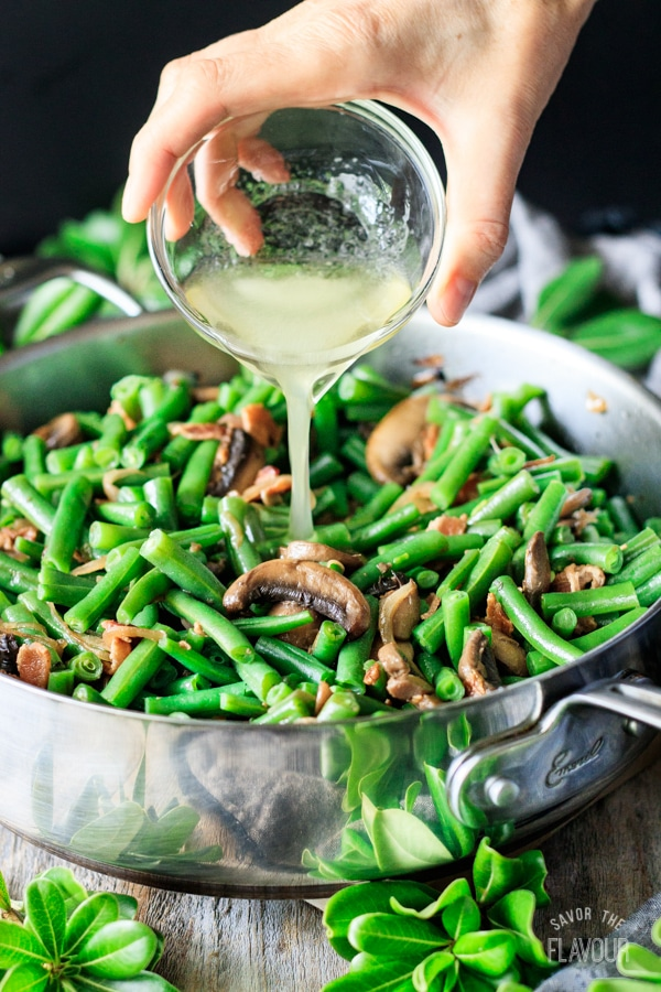 pouring dressing on green beans with bacon and mushrooms