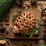 closeup of woodland hedgehog cheese ball with rosemary sprigs and a bowl of crackers
