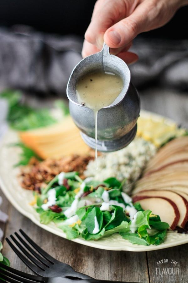 pouring salad dressing over salad