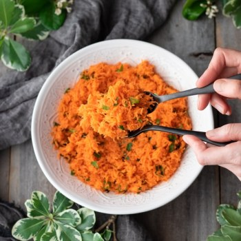 person lifting a bunch of French grated carrot salad