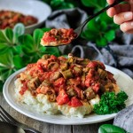 a forkful of skillet Southern okra and tomatoes with greenery